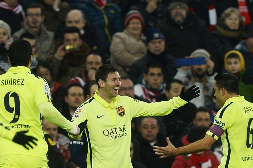 (From left) Barcelona's Luis Suarez, Lionel Messi and Xavi Hernandez celebrating a goal by Messi during their match against Athletic Bilbao at San Mames stadium in Bilbao on Feb 8, 2015. -- PHOTO: REUTERS