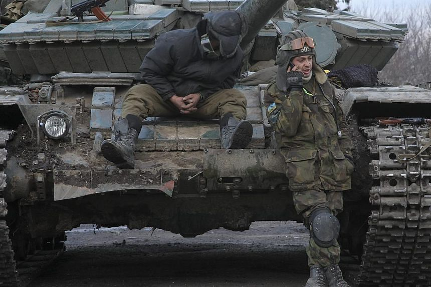 Ukrainian servicemen rest on a tank in Artyomovsk of Donetsk area, Ukraine on Sunday as world leaders met in Munich to try to broker a peace deal. -- PHOTO: EPA