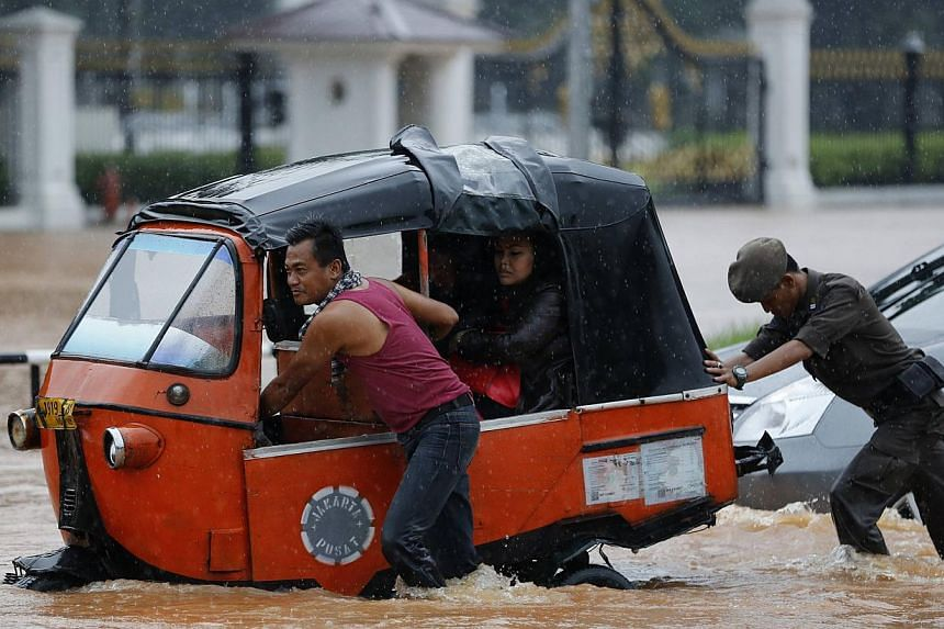 A driver pushing his Baja vehicle through flood waters outside the Presidential Palace, after heavy seasonal rains flooded parts of Jakarta on Feb 9, 2015. -- PHOTO: REUTERS