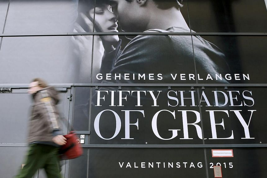 A pedestrian walks past an advertising placard for the movie 'Fifty Shades of Grey' which will be screened at the upcomming 65th Berlinale International Film Festival in Berlin on Feb 4, 2015. --PHOTO: REUTERS