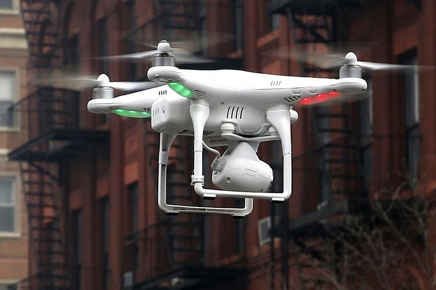 A camera drone operated by a civilian flies near the scene where two buildings were destroyed in an explosion in New York, in this file photo taken on March 12, 2014.Between 20 and 30 per cent of 70 applications for permits to fly drones in Sin