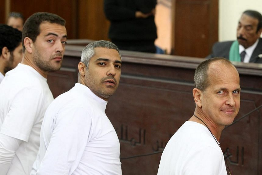 (From right) Australian journalist Peter Greste, Canadian-Egyptian journalist Mohamed Fahmy and journalist Baher Mohamed stand in front of the judge's bench during their trial for allegedly supporting a terrorist group and spreading fa