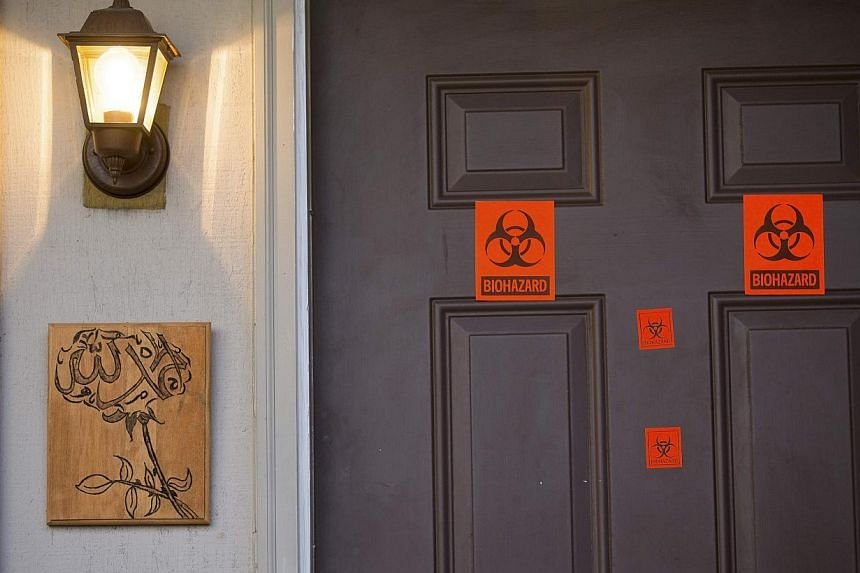 A view of the front door, which now has biohazard stickers, of the apartment where three young Muslims were killed on Tuesday, in Chapel Hill, North Carolina, on Feb 11, 2015. -- PHOTO: REUTERS