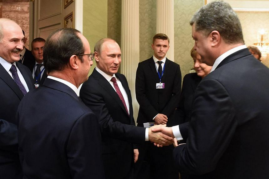 Russian President Vladimir Putin (centre) shakes hands with Ukrainian President Petro Poroshenko (right) during a meeting on February 11, 2015, in Minsk, aimed at halting a 10-month war in Ukraine where dozens were killed in the latest fighting. Russ
