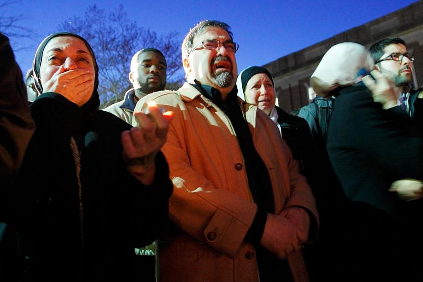 Namee Barakat (centre) and his wife Layla Barakat (centre, rear), parents of shooting victim Deah Shaddy Barakat, during a vigil in Chapel Hill. -- PHOTO: JONATHAN DRAKE FOR THE STRAITS TIMES