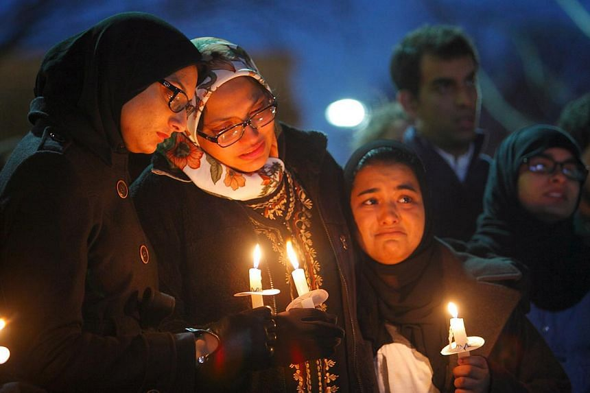 Family, friends and well-wishers at a vigil for the victims. -- PHOTO: JONATHAN DRAKE FOR THE STRAITS TIMES