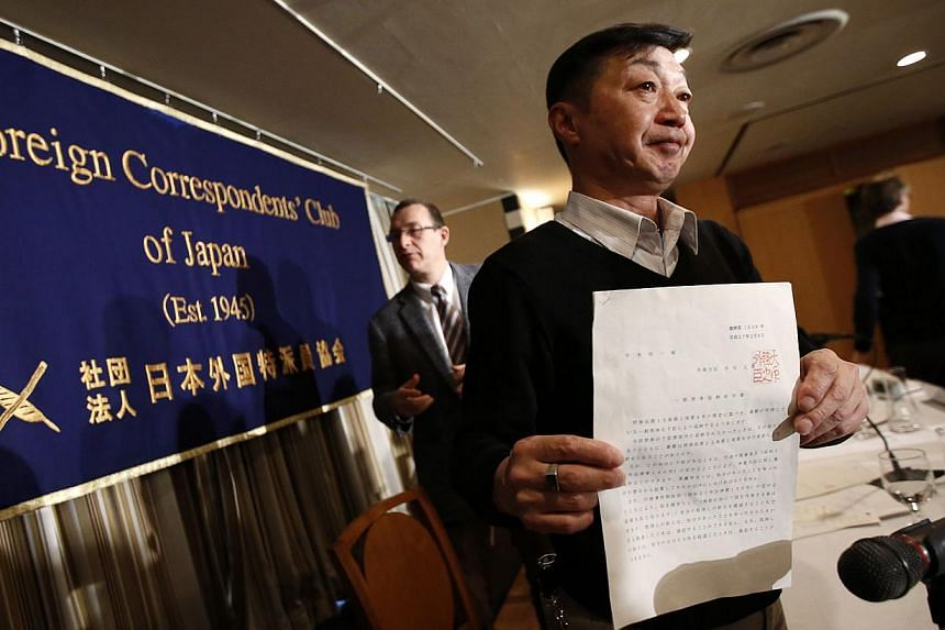 Japanese freelance photographer Yuichi Sugimoto (right) shows a mandate letter issued by Foreign Minister Fumio Kishida during a news conference at the Foreign Correspondents' Club of Japan in Tokyo Feb 12, 2015. Sugimoto accused the government
