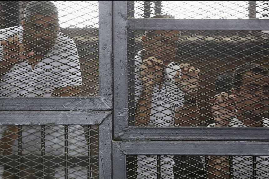 Al-Jazeera journalists (from left) Mohamed Fahmy, Peter Greste and Baher Mohamed standing behind bars at a court in Cairo in this May 15, 2014 photo. -- PHOTO: REUTERS