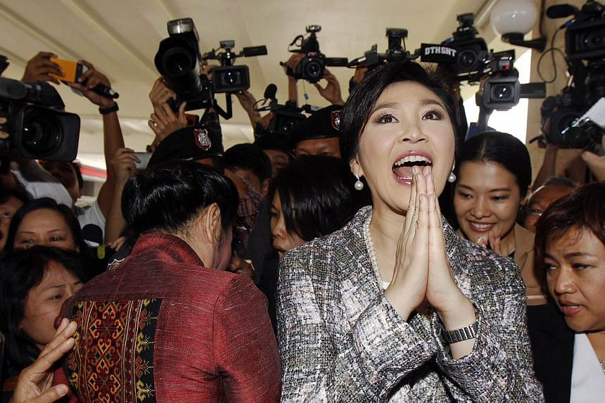 Ousted former Thai Prime Minister Yingluck Shinawatra gives a traditional greeting as she leaves parliament in Bangkok on Jan 22, 2015. Thailand's junta chief on Thursday, Feb 12, 2015, said the military is keeping such a close eye on