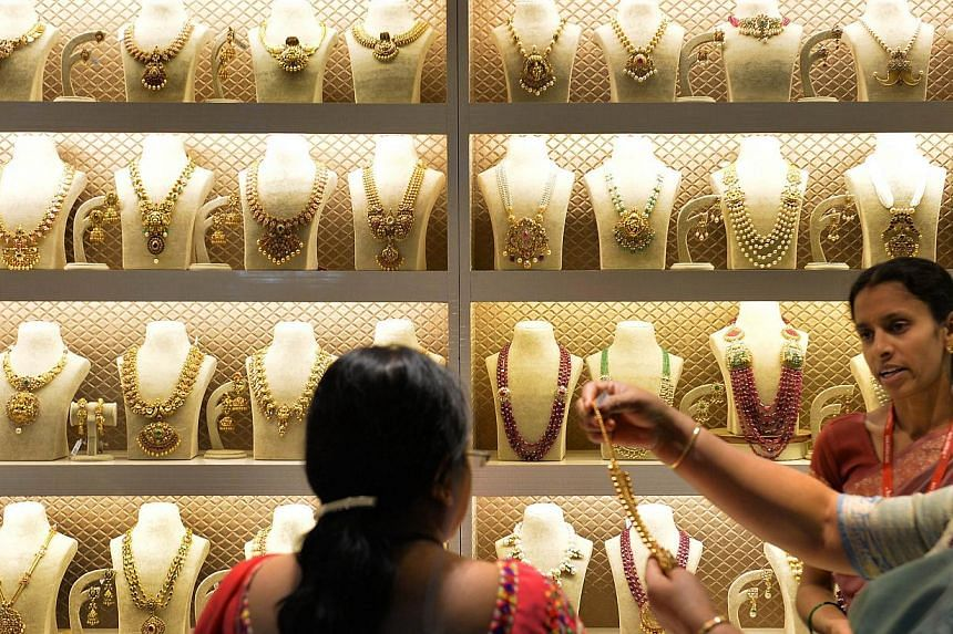 Indian residents examine gold jewellery at a stall during the 'Asia Wedding Fair 2015' in Bangalore on Feb 6, 2015. Gold demand fell for a third year on a slump in purchases from China, costing the country its place as the world's biggest buyer to In
