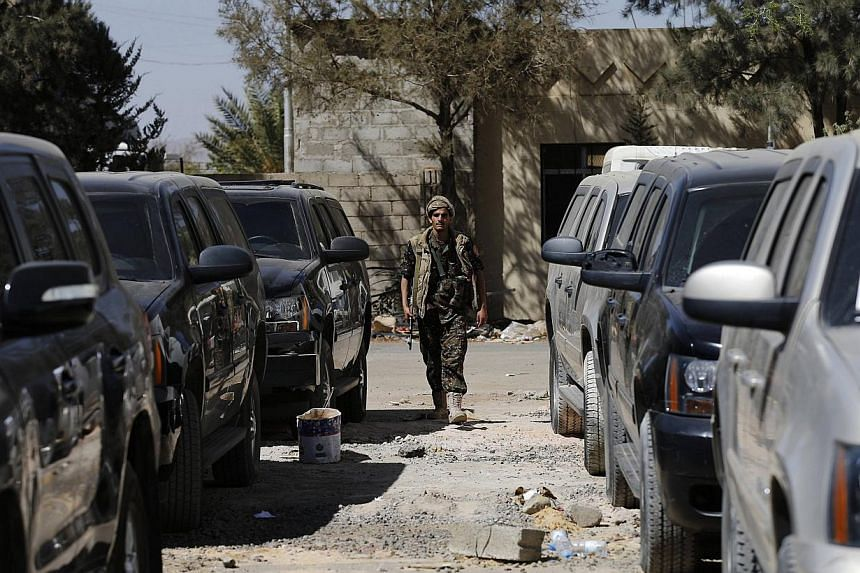 A police trooper walks past armoured US embassy cars, seized by Houthi rebels, at Sanaa airport Feb 12, 2015. -- PHOTO: REUTERS