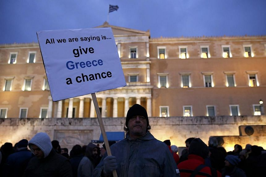 A protester displays his sign during an anti-austerity, pro-government demonstration outside the Greek parliament in Athens on the eve of a crucial euro zone finance minister's meeting to discuss the country's future, Feb 11, 2015. -- PHOTO: REUTERS
