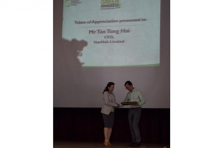 StarHub CEO Tan Tong Hai receiving a token of appreciation from Singapore Environment Council chairman Isabella Loh. -- ST PHOTO: AUDREY TAN
