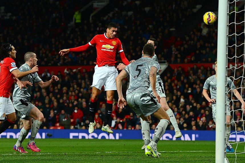 Manchester United's Chris Smalling (centre) heads to score the 2-1 lead during their match against Burnley FC at Old Trafford on Feb 11, 2015. United beat struggling Burnley 3-1 on Wednesday but for large parts of the match were outplayed. -- PH