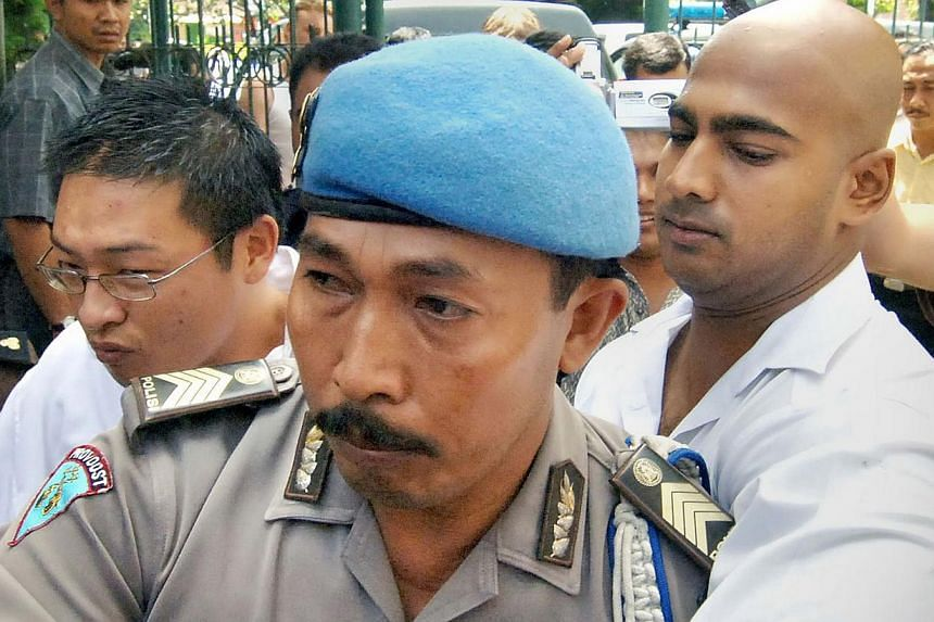"""In this file photo taken on Feb 14, 2006, convicted Australian drug smugglers Myuran Sukumaran (left) and Andrew Chan (right), the leaders of the so-called """"Bali Nine"""" drug-smuggling gang, are escorted by an Indonesian policeman (centre) to a court t"""