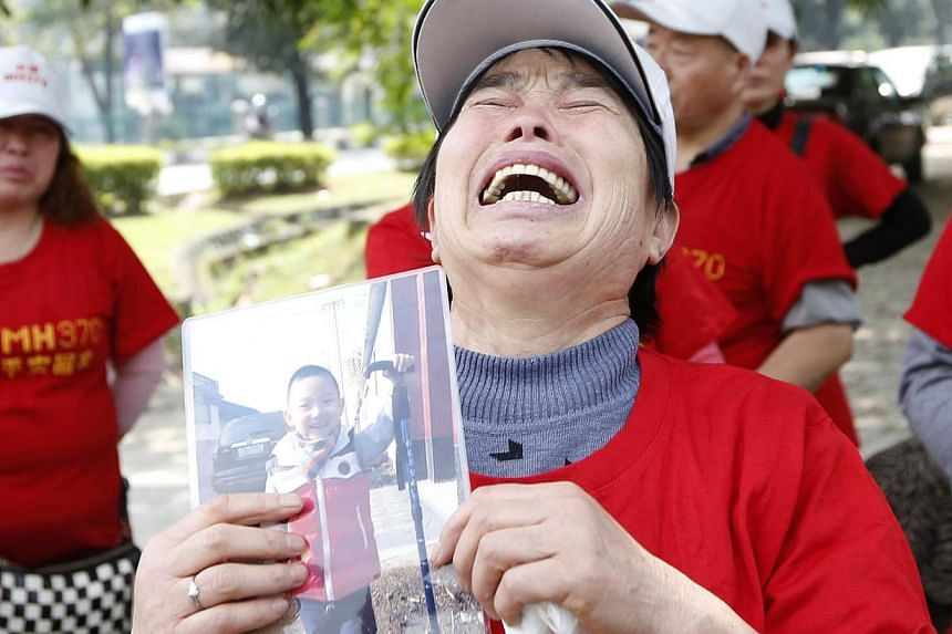 The mother of a passenger of missing Malaysia Airlines Flight MH370 holding a picture of her grandson outside the Malaysia Airlines headquarters in Kuala Lumpur on Feb 12, 2015. -- PHOTO: REUTERS