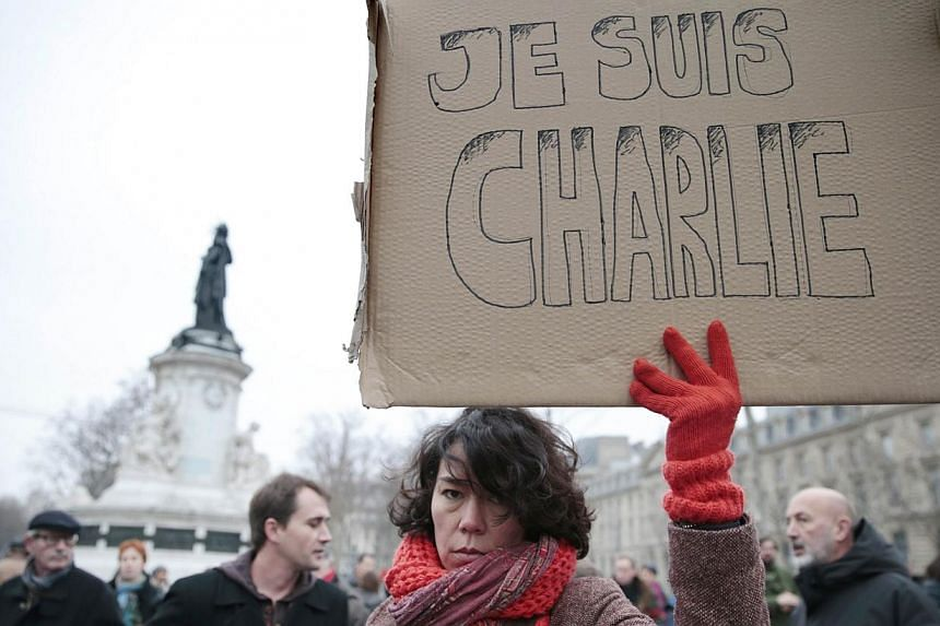 "A woman holds up a placard that reads in French, ""I am Charlie"" at a gathering in Paris on Jan 7, 2015, following Islamist attacks on the French capital. Paris City Hall on Wednesday decided to launch a lawsuit over reports by US news channel Fox New"