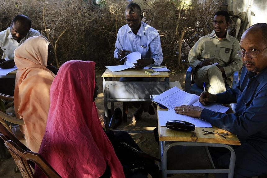 Special prosecutor for crimes in Darfur Yasir Ahmed Mohamed (right) and his team talk to women during an investigation into allegations of mass rape in the village of Tabit, in North Darfur, Nov 20, 2014. -- PHOTO: REUTERS