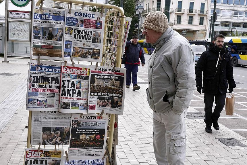 A man reds newspaper's headlines at a news stand in Athens on Feb 12, 2015The European Central Bank has increased the volume of emergency liquidity available to Greek banks by €5 billion (S$7.7 billion) , two newspapers reported on Thursday.