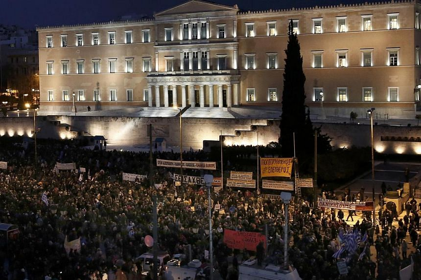People gather for an anti-austerity, pro-government demonstration outside the Greek parliament in Athens on the eve of a crucial euro zone finance minister's meeting to discuss the country's future, on Feb 11, 2015. -- PHOTO: REUTERS