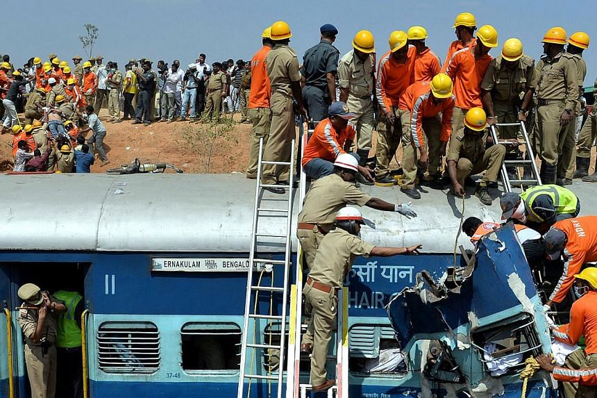 Crowds watch as Indian fire force personnel attempt to retrieve the bodies of victims from the Bangalore-Ernakulam train which derailed after a boulder fell on the track in Bidaragere, about 50 kms from Bangalore on Feb 13, 201. At least five passeng