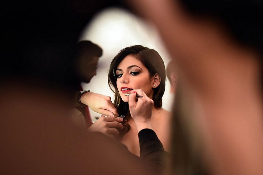 A model gets ready backstage for the Go Red For Women Red Dress Collection 2015 presented by Macy's during Mercedes-Benz Fashion Week Fall 2015 at the The Lincoln Center in New York on Feb 12, 2015. -- PHOTO: AFP