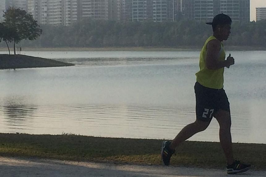 Joggers seen at Bedok Reservoir on Friday morning. The PSI reached 79 in eastern parts of Singapore on Friday morning. -- ST PHOTO: SEAH KWANG PENG