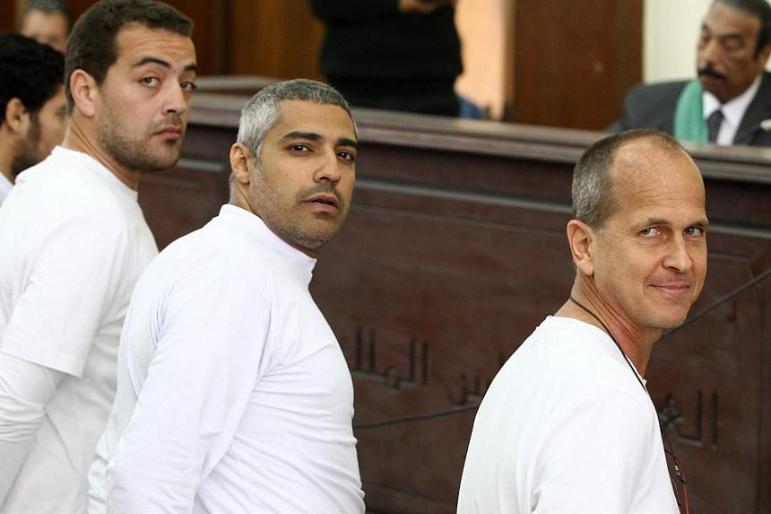 A March 31, 2014 photo shows Australian journalist Peter Greste (right), Canadian-Egyptian journalist Mohammed Fahmy (centre) and journalist Baher Mahmoud (left) on trial in Cairo, Egypt. -- PHOTO: EPA