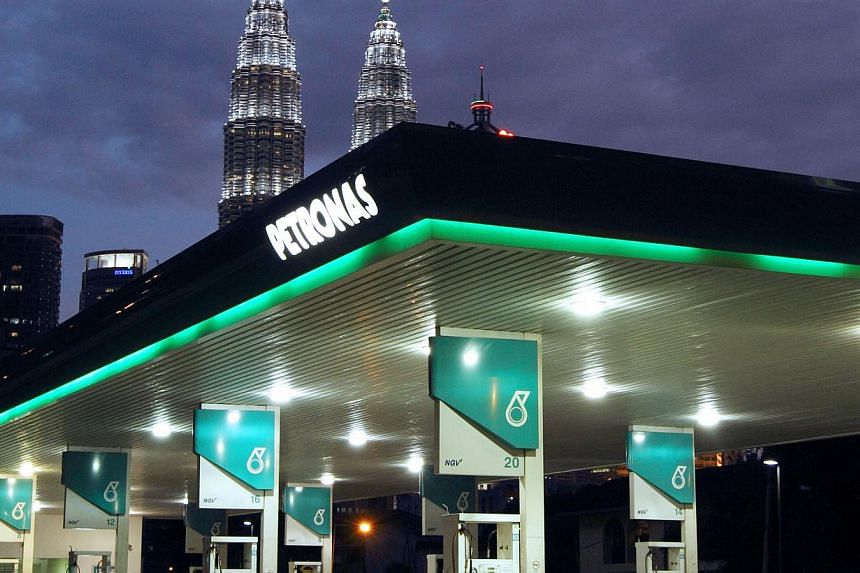A Petronas petrol station is pictured in front of the Petronas Twin Towers in Kuala Lumpur. Malaysia's national oil company is paying for troubles at state investment fund 1MDB. -- PHOTO: BLOOMBERG
