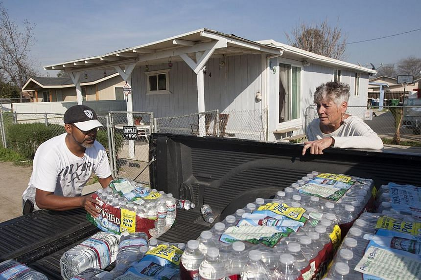 Donna Johnson (right) distributing drinking water to neighbours in East Porterville, California, on Feb 11, 2015, as water wells supplying hundreds of residents there remain dry in the fourth year of worsening drought. -- PHOTO: AFP