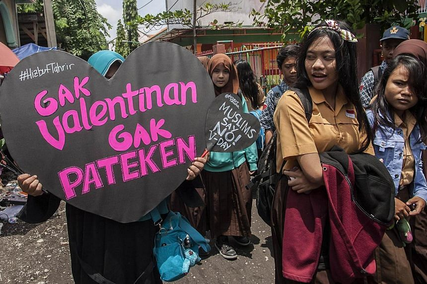 A member of Indonesia's conservative Islamic organization Hizbut Tahrir holds a placard during an anti-Valentine's Day protest outside a school in Surabaya city, eastern Java island on Feb 13, 2015. Indonesia's top Islamic clerical body threatened Fr