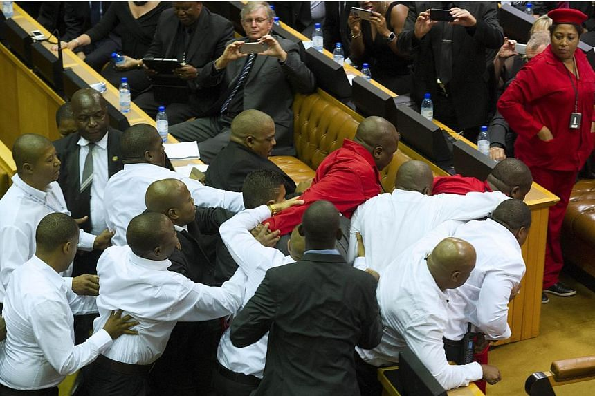 Members of the Economic Freedom Fighters, wearing red uniforms, clash with security forces during South African President's State of the Nation address in Cape Town on Feb 12, 2015.South Africa was Friday evaluating its hard-won democracy, embo