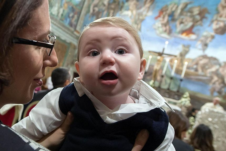 A woman holding a baby at the Vatican onJan 11, 2015, as Pope Francis delivers a speech.Fewer babies were born in Italy in 2014 than in any other year since the modern Italian state was formed in 1861, new data shows, highlighting the dem