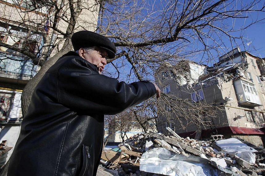 A local resident points at a house damaged by a shelling in the town of Dokuchayevsk, south of Donetsk, Feb 12, 2015. -- PHOTO: REUTERS