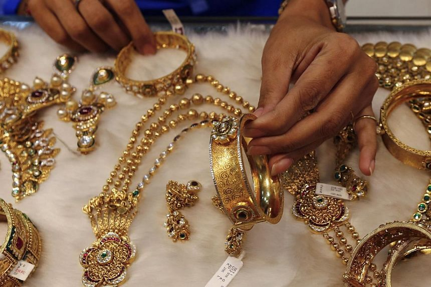 A woman looks at a gold bangle inside a jewellery showroom at a market in Mumbai Jan 15, 2015.China lost its place to India as the world's biggest gold consumer in 2014, sector data showed Thursday, hit by collapsing jewellery demand after one