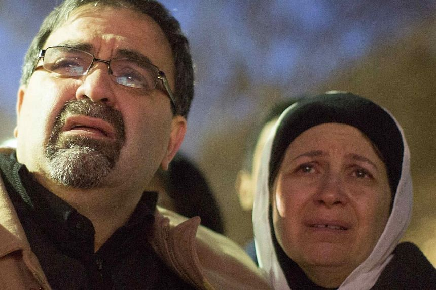 Namee Barakat and his wife Layla Barakat, parents of shooting victim Deah Shaddy Barakat, react as a video is played during a vigil on the campus of the University of North Carolina in Chapel Hill, North Carolina Feb 11, 2015. -- PHOTO: REUTERS
