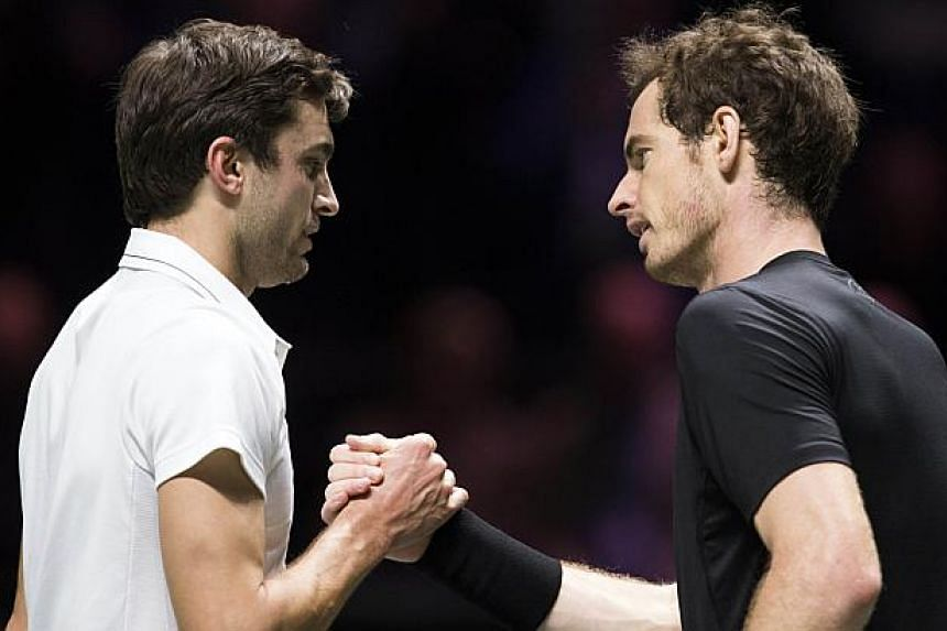 Gilles Simon (left) of France and Britain's Andy Murray shake hands at the end of their quarter-final match in Rotterdam on Feb 13, 2015. -- PHOTO: AFP