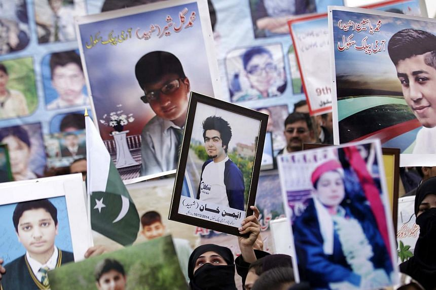 Relatives of students killed by Taleban militants during a December massacre at a school in Pakistan hold photos depicting the victims during a protest demanding that the culprits of the attack be brought to justice on Feb 7, 2015. -- PHOTO EPA