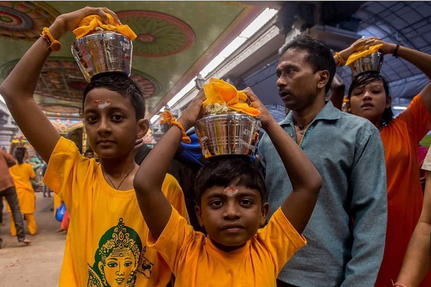Young children carrying palkudam during the Thaipusam procession on Jan 17, 2014. The Ministry of Manpower (MOM) has issued a response on whether Thaipusam should be reinstated as a public holiday. -- PHOTO: TAMIL MURASU