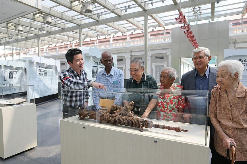 Alvin Tan (left), group director of policy at National Heritage Board, speaking to WWII survivors about the remains of a Japanese Model 92 heavy machine gun used during WWII, which was recovered in Singapore in 2002.-- ST PHOTO:ONG