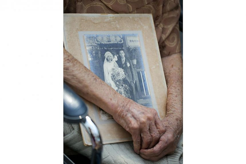 Chia Siok Hew, 92, holding on to her wedding photo taken at the front porch of the family house at Chia Keng Village in 1939 as she recounts old stories during the war.-- ST PHOTO:ONG WEE JIN