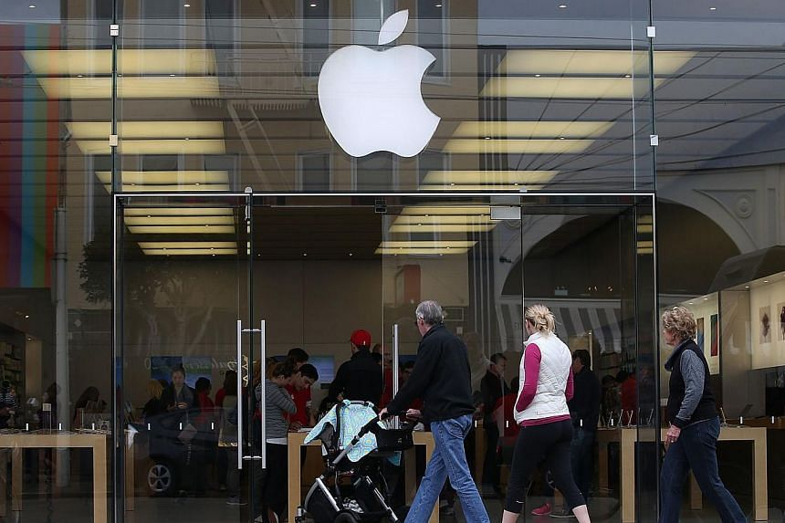 Customers entering an Apple Store on Jan 27, 2015, in San Francisco, California. The tech giant is reportedly learning how to make a self-driving electric car. -- PHOTO: AFP