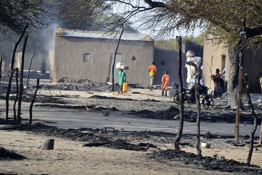 People walk in a burnt compound after an attack by Boko Haram militants in the village of Ngouboua onFeb 13, 2015. The group then attacked the northeastern Nigerian city of Gombe on Saturday. -- PHOTO: REUTERS