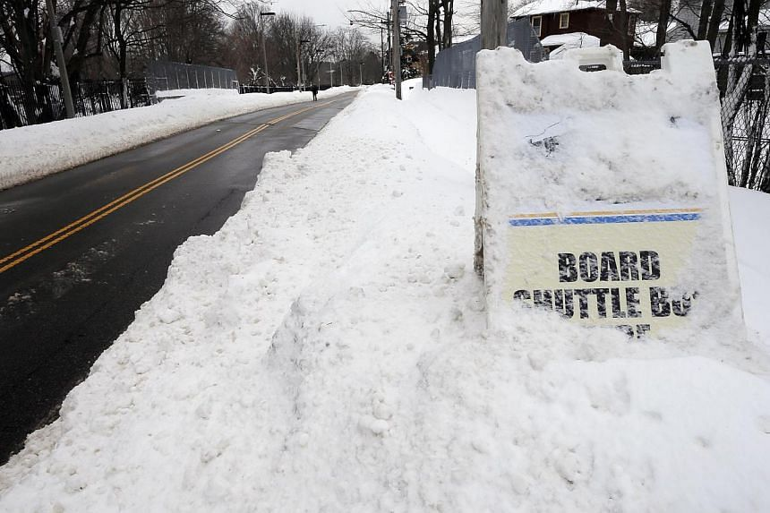 A sign in a snow drift marks the shuttle bus service at the closed MBTA subway station in Boston, Massachusetts on Feb 10, 2015. -- PHOTO: REUTERS