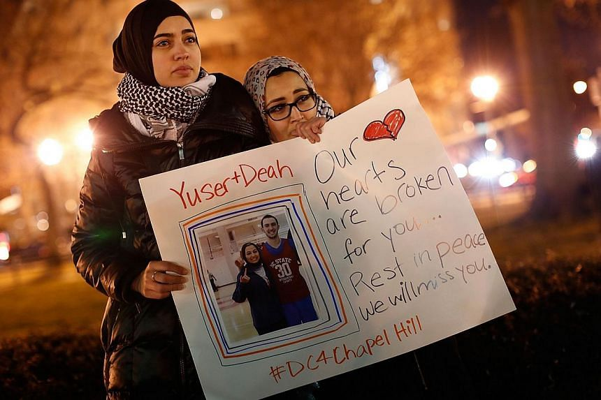 Kheira Benkreira (left) and Hasnia Bekkadja attend a vigil held by the Council on American-Islamic Relations in Dupont Circle in Washington, DC on Feb 12, 2015. -- PHOTO: AFP