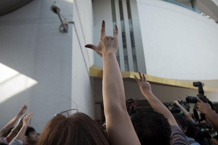 Demonstrators gesture as an activist (not seen) is arrested by police officers while he was making a speech outside the Art and Cultural centre during a rally in Bangkok on Feb 14, 2015. -- PHOTO: AFP