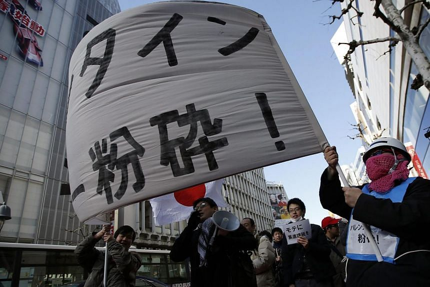 "Protesters holding a banner reading ""Smash Valentine's Day"" as they shout slogans during a march at Tokyo's Shibuya shopping and amusement district on Feb 14, 2015. -- PHOTO: REUTERS"