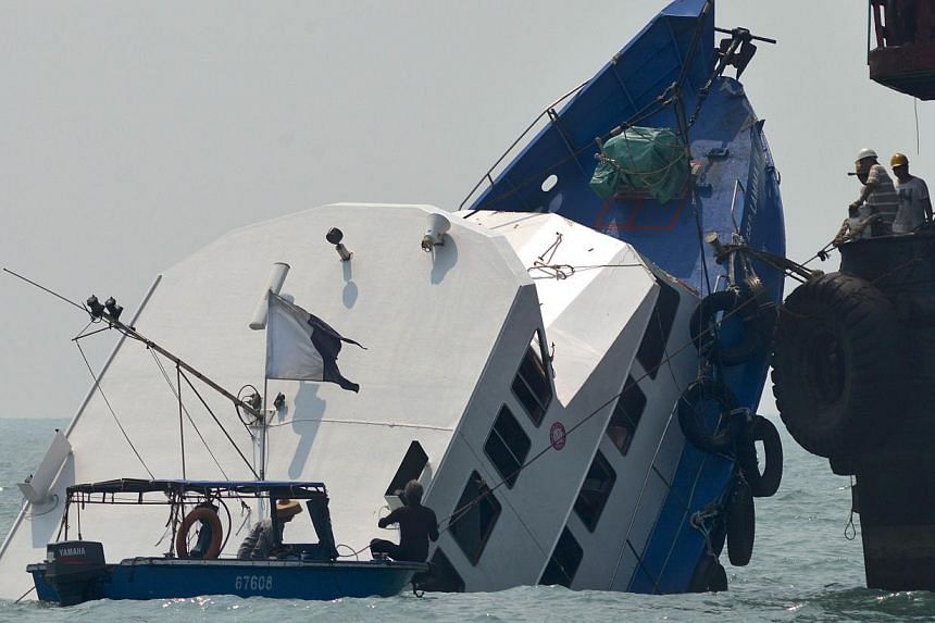 The bow of the Lamma IV boat is shownpartially submerged during rescue operations the morning after it collided with a Hong Kong ferry on Oct 2, 2012. -- PHOTO: AFP