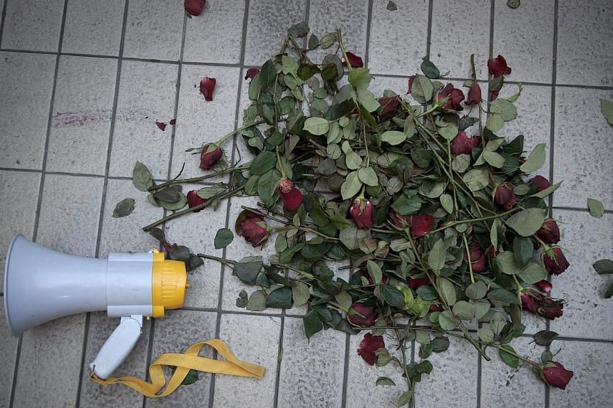Roses and a megaphone used by a demonstrator lie on the floor after he was arrested by police officers while making a speech outside the Art and Cultural centre during a rally in Bangkok on Feb 14, 2015. -- PHOTO: AFP