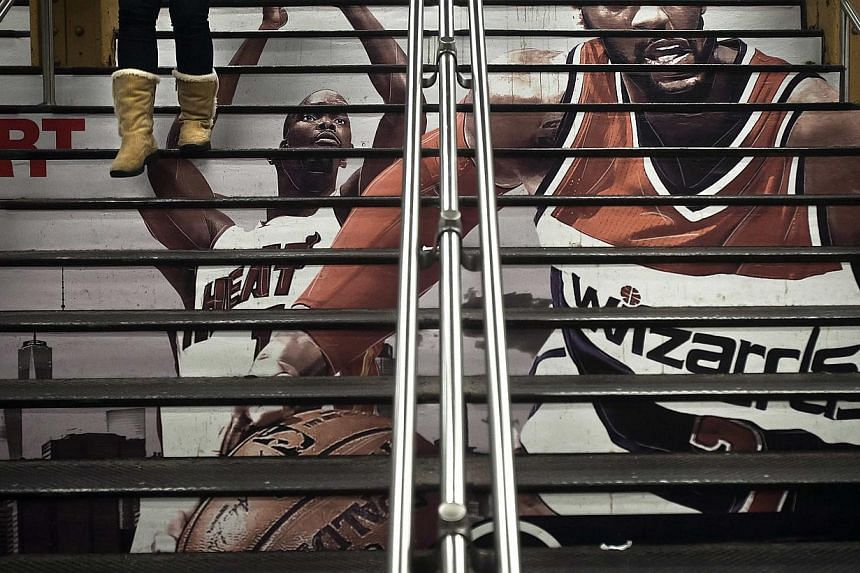 A woman walks down a flight of stairs with an advertisement for the upcoming NBA All-Star Game, in Grand Central Terminal in the Manhattan borough of New York on Feb 2, 2015. -- PHOTO: REUTERS
